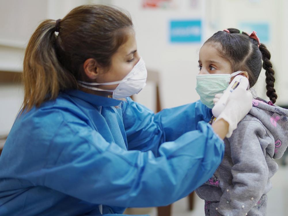 A nurse takes a girl's temperature at a Primary Health Care Centre in Beirut, Lebanon.