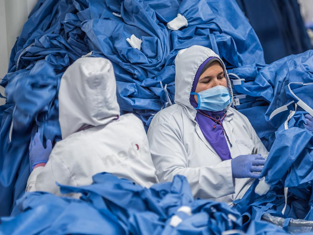 Humanitarians sorting through a large pile of blue surgical gowns to support and protect Egyptian healthcare workers.